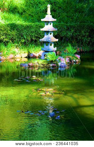 Koi Pond Surrounded By Lush Green Gardens And Sculptures Taken At A Zen Meditation Garden