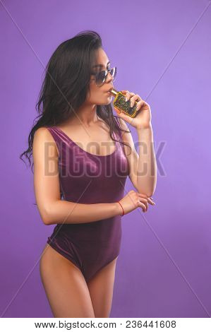 Young Sexy Woman In Purple Body And Sunglasses Is Vaping. A Cloud Of Vapor. Studio Shooting. Purple