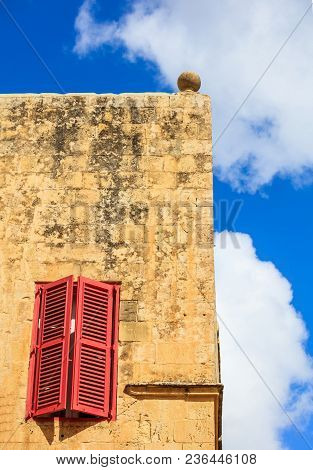 Malta, Mdina. Red Window On A Yellow Sandstone Wall In The Old Medieval City. Blue Sky Background