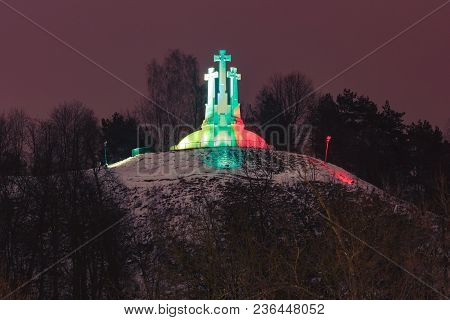 Three Crosses On The Bleak Hill Illuminated By The Colors Of The National Lithuanian Flag At Night O