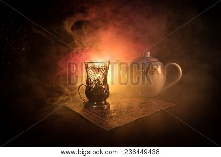 Eastern Tea In Traditional Glasse And Pot On Black Background With Lights And Smoke. Eastern Tea Con