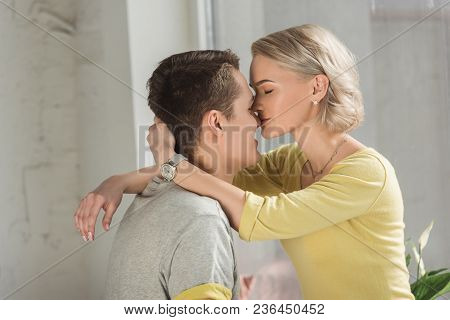 Side View Of Girlfriend Kissing Boyfriends Nose At Home