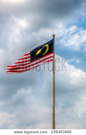 Malaysia Flag Also Known As Jalur Gemilang Wave With The Blue Sky. People Fly The Flag In Conjunctio