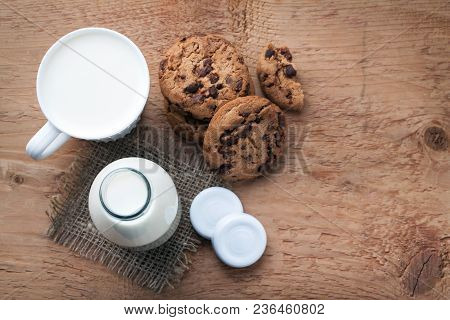 Two Bottles Of Milk And Chocolate Chip Cookies On Dark Background With Copy Space. Top View.