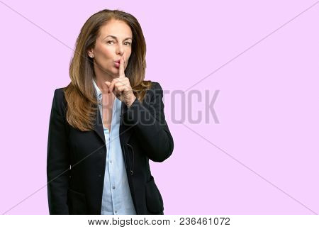 Middle age business woman with index finger on lips, ask to be quiet. Silence and secret concept