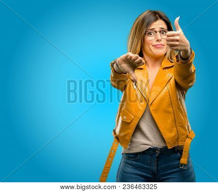 Beautiful young woman confused with thumbs up and down, trying to take a decision expressing doubt and frustration, blue background