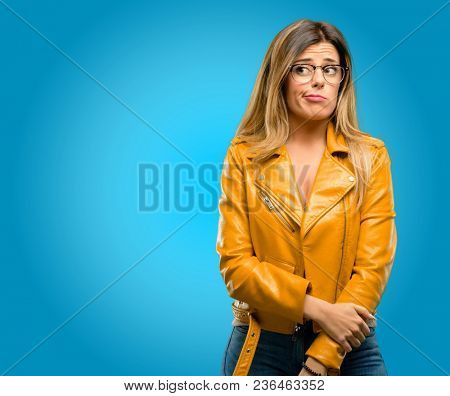 Beautiful young woman doubt expression, confuse and wonder concept, uncertain future, blue background