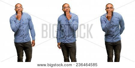 African american man with beard covers mouth in shock, looks shy, expressing silence and mistake concepts, scared
