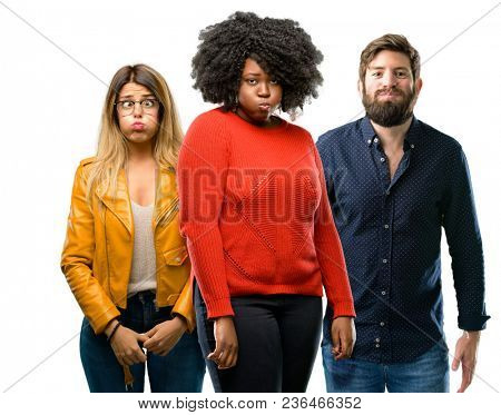Group of three young men and women puffing out cheeks, having fun making funny face