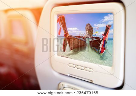 Aircraft In Flight Entertainment Seat-back Tv Screens Showing A Picture Of Long Tail Boat And Beauti