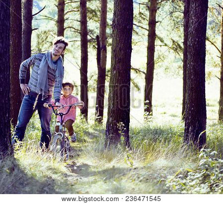 Father Learning His Son To Ride On Bicycle Outside, Real Happy Family In Summer Forest Enjoing Natur