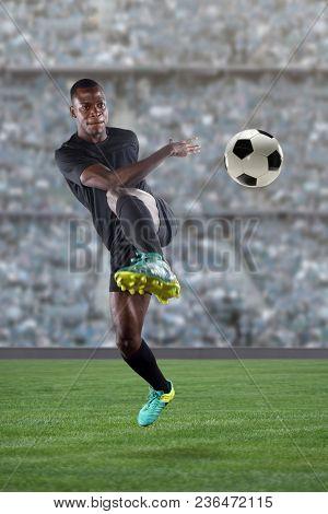African American soccer player kicking ball inside large stadium