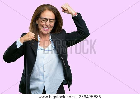 Middle age business woman happy and excited expressing winning gesture. Successful and celebrating victory, triumphant