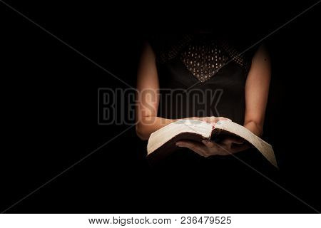 A Woman Reading The Holy Bible In A Dark Background .