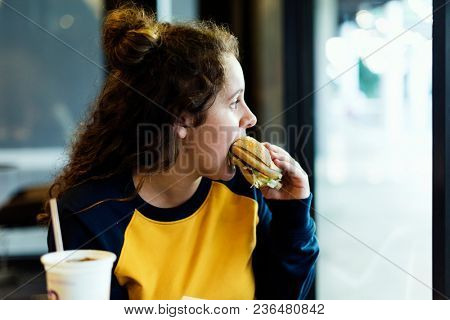 Close up of teenage girl eating hamburger obesity concept