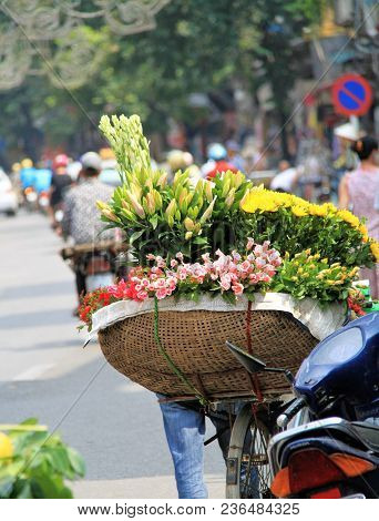 Vibrant Fresh Colour Of Flowers Arranged In Basket On Back Of Bicycle With Streetscape Of Motorbikes