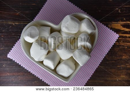 Fluffy White Marshmallow In Heart Shapedd Bowl On Old Wooden Table