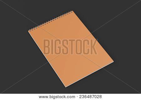 Blank Orange Notebook With Metal Spiral Bound On Black Background
