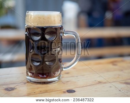 German Glass Beer Mug Filled With A Dark Ale Sitting On Wooden Table