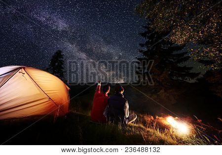 Back View Male Hiker Showing Female Up On The Evening Starry Sky At Milky Way. Couple Sitting In The