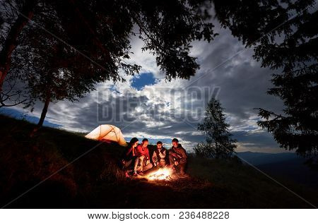 Four Person Tourists Are Sitting Around A Campfire With A Beer Near The Camping And Forest At Night