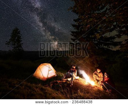 Two Couples At Campfire Enjoying The Starry Sky With Milky Way. One Pair Sitting On Log Beside Orang