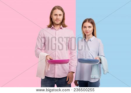 We Love Cooking. Upbeat Young Couple Holding Frying Pans And Kitchen Towels, Being Ready To Cook Som