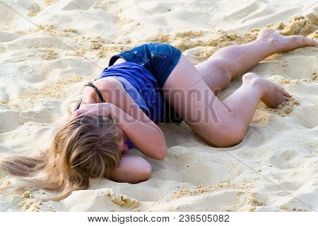 Moscow Region, Russia, June 4, 2013: Long-haired Blonde Lies On The Sand.
