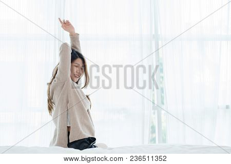 Back View Of Happy Beautiful Young Asian Woman Waking Up In Morning, Sitting On Bed, Stretching In C