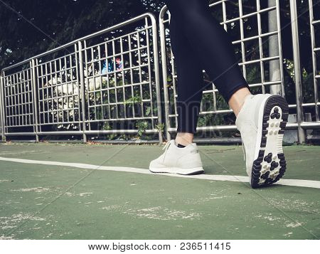 Young Asian Woman Running On Sidewalk In Morning. Health Conscious Concept With Copy Space. Young Sp