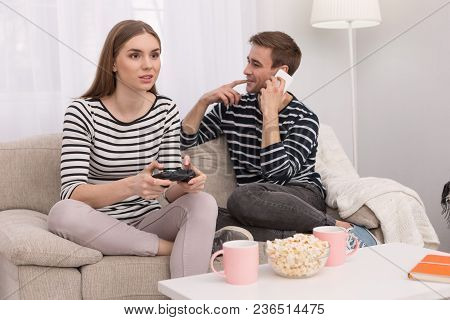 I Love Playing. Joyful Concentrated Woman Playing A Game And Her Boyfriend Talking On The Phone