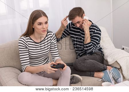 Good Gamer. Cheerful Concentrated Woman Playing A Game And Her Boyfriend Talking On The Phone