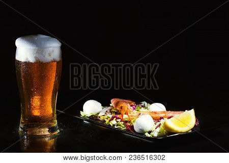 Glass Of Light Beer And Salad With Argentine Red Shtimp. Photo On Dark Background. Copy Space