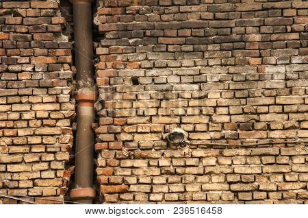 Old Grunge Weathered Brickwall With Stoneware Vitrified Clay Ceramic Drain Sewer Pipe Closeup