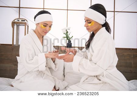 Professional Skincare. Nice Pretty Women Sitting Together And Using Hand Cream
