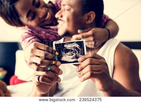 Black couple showing baby ultrasound scan photo