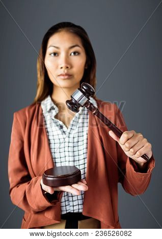 Female judge with gavel against grey background