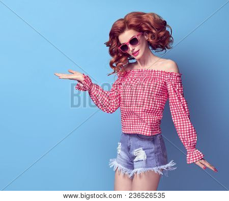 Fashion Pretty Pinup Redhead Girl Smiling Having Fun. Presenting Your Product. Trendy Curly Hairstyl