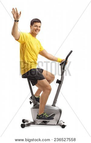 Young man exercising on a stationary bike and waving at the camera isolated on white background