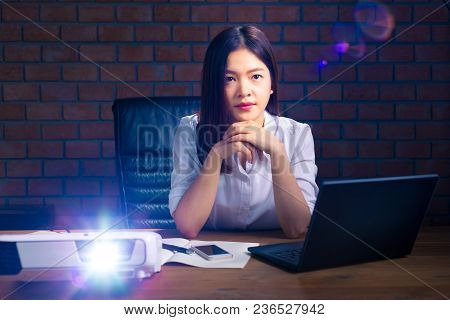 Young Attractive And Successful Asian Executive Woman Watching Presentation Projected On Screen In H