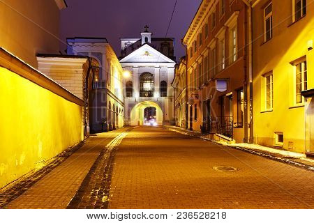 Picturesque Street And Gate Of Dawn At Night In Old Town Of Vilnius, Lithuania, Baltic States. The I