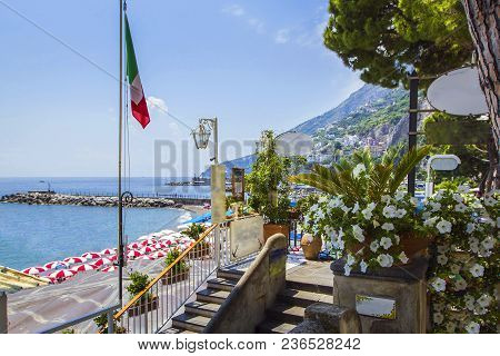 View Of Coast Amalfi, Beach, Sea And Mountains With Embankment Decorated With Flowers And Palm Trees
