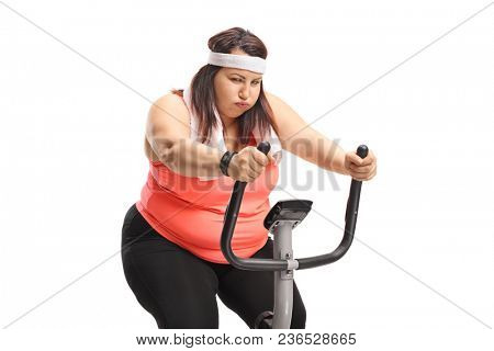 Exhausted overweight woman exercising on a stationary bike isolated on white background