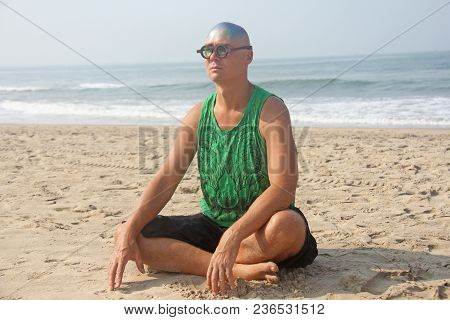 A Bald And Unusual Young Man, A Freak, With A Shiny Bald Head And Round Wooden Glasses On The Backgr