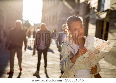 Gorgeous female tourist with a map discovering a foreign city (shallow DOF; color toned image) backlit by warm evening sunshine