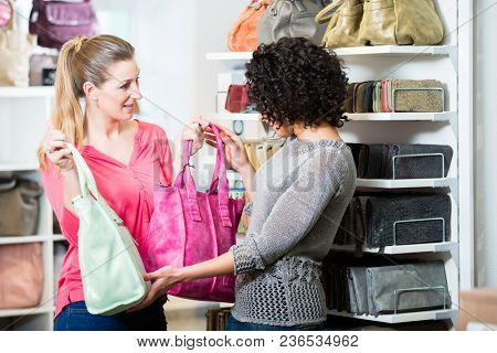 Girlfriends in fashion store buying leather handbag
