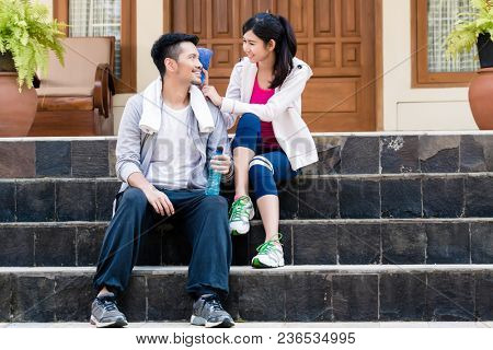 Young woman wiping away the sweat from the face of her boyfriend after outdoors workout session