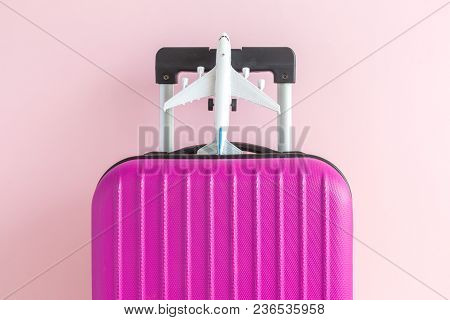 Suitcase And Airplane Model On Pastel Pink Background Minimal Creative Travel Concept