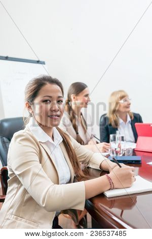 Portrait of a confident Asian business woman wearing formal outfits, while sitting down during a decision-making meeting in the conference room of a successful company