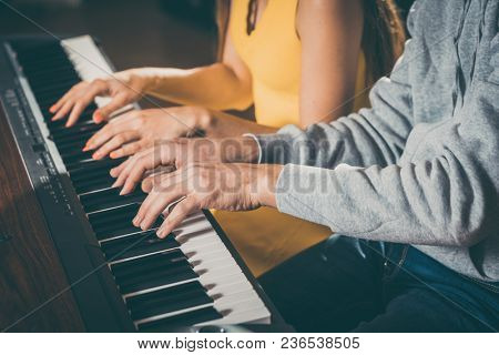 Piano players playing together four-handed piece during music school rehearsal